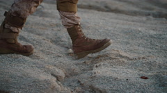 Close-up shot of Walking Soldier's Legs in Desert Environment.  Stock Footage