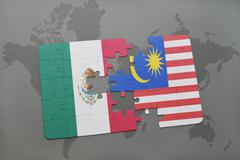 Puzzle with the national flag of mexico and malaysia on a world map backgroun Stock Photos