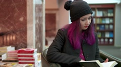 Alternative girl reads book in supermarket Stock Footage