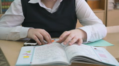 Pupil flips pages of tutorial during the lesson Stock Footage