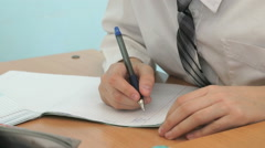 The schoolboy writing the text in the copybook Stock Footage