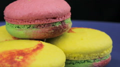 Multicolored macaroon rotating on a dark background, close-up Stock Footage
