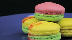 Multicolored macaroon revolve a clockwise on a dark background, close-up Stock Footage