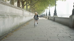 4K Cheerful London businesswoman cycling in the city. Stock Footage
