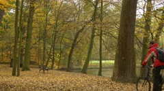 Man is Riding a Bicycle by Bench in Alley Autumn Landscape Cyclist Spends Time Stock Footage