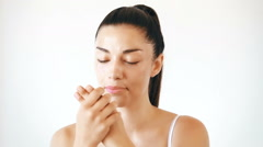 Portrait of beautiful woman applying cream on her face Stock Footage
