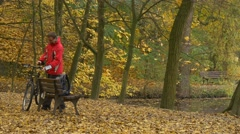 Cyclist Comes Placed His Bike Sits Down to Bench Autumn Day Man is Resting Stock Footage