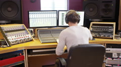 4K Portrait smiling sound engineer working at mixing desk in recording studio Stock Footage