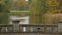 Brick Bridge Over River Lake Cloudy Day in Autumn Green and Yellow Trees Lawn Stock Footage