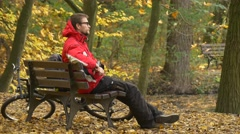 Man in Glasses Sitting on Bench Thinking Autumn Day Cyclist is Resting Among Stock Footage