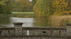 Old Brick Bridge Over River Lake Cloudy Day Autumn Green and Yellow Trees Lawn Stock Footage