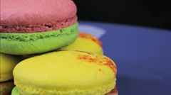 Pink, yellow and green macaroon rotate against a dark background, close-up Stock Footage
