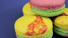 Pink, yellow and green macaroon quickly rotate on a blue plate, close-up Stock Footage