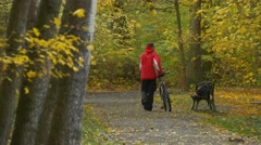 Man Comes Places a Bicycle Sits Down to Bench Autumn Day in Park Alley Stock Footage