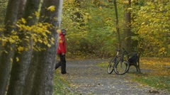 Tourist Comes Sits Down to Bench in Park Bicycle Placed at the Bench Autumn Day Stock Footage