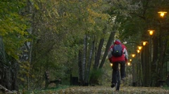 Man is Riding a Bicycle Away View of Alley Autumn Day Yellow Leaves on the Stock Footage