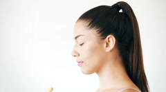 Profile of attractive woman applying powder on her face Stock Footage