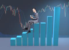 Businessman sitting on bar charts in business concept Stock Photos