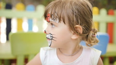 Little girl get painted face as a cat for a carnival Stock Footage