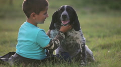 Boy on the grass hugging dog and sing a lullaby Stock Footage