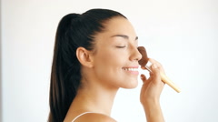 Close up profile of smiling woman applying powder on her face Stock Footage