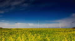Landscape with windmills and blooming rapeseed field in 4k timelapse.  Stock Footage