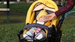 Baby sitting in the baby carriage, mother gives the bottle with water Stock Footage
