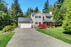 Beautiful curb appeal  of suburban two story house with well kept lawn and fi Stock Photos