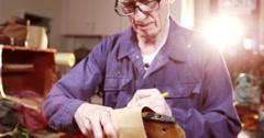 Shoemaker marking a piece of leather on shoe last Stock Footage