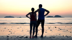 Couple of joggers resting and admire sunset on beach  Stock Footage