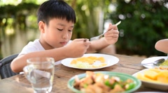 Young Thai boy eating with food on the wooden table Stock Footage