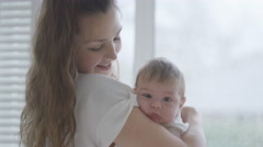 4K Portrait of new mother holding baby daughter at home, in soft natural light Stock Footage