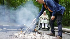Disabled elderly woman rest next to bonfire in a forest Stock Footage