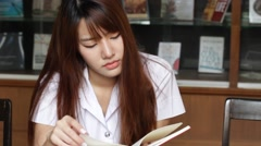 Thai adult student university uniform beautiful girl reading red book Stock Footage
