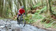 Mountain biker riding bicycle in creek Stock Footage