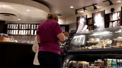 Close up people buying coffee and paying by credit card inside Starbucks store Stock Footage