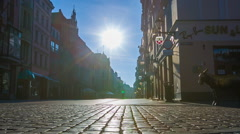 Old city paving stone street with pedestrians, sun light Stock Footage