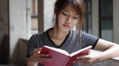 Portrait of thai adult beautiful girl reading red book Stock Footage