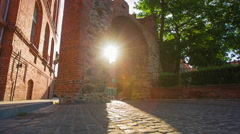 Old city paving stone street with pedestrians, sun light and ancient arch Stock Footage