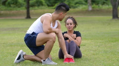 Wide shot man holding womans feet while she is doing situps in a park Stock Footage