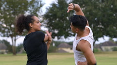 Two people stretching after exercising in a park Stock Footage
