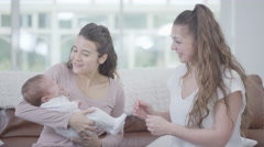 4K New mother with friend or family member holding cute baby daughter at home Stock Footage
