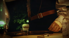 Old west gunman loading his pistol and checking the time Stock Footage