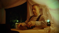 Eighteenth century man reading a bible in a tent Stock Footage