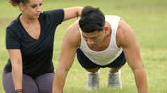 Close shot woman helping her male friend do pushups outdoor Stock Footage