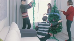 Friends decorating a christmas tree in a living room timelapse stopmotion Stock Footage