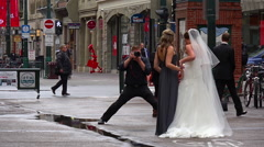 Photographer and wedding party, taking formal photos in a downtown setting Stock Footage