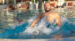Young, happy man having fun in pool, super slow motion 240fps Stock Footage