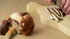 Woman is cutting fresh bay bolete mushroom into slices Stock Footage