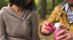 Guy pours tea from thermos in woods and gives it to his girl Stock Footage